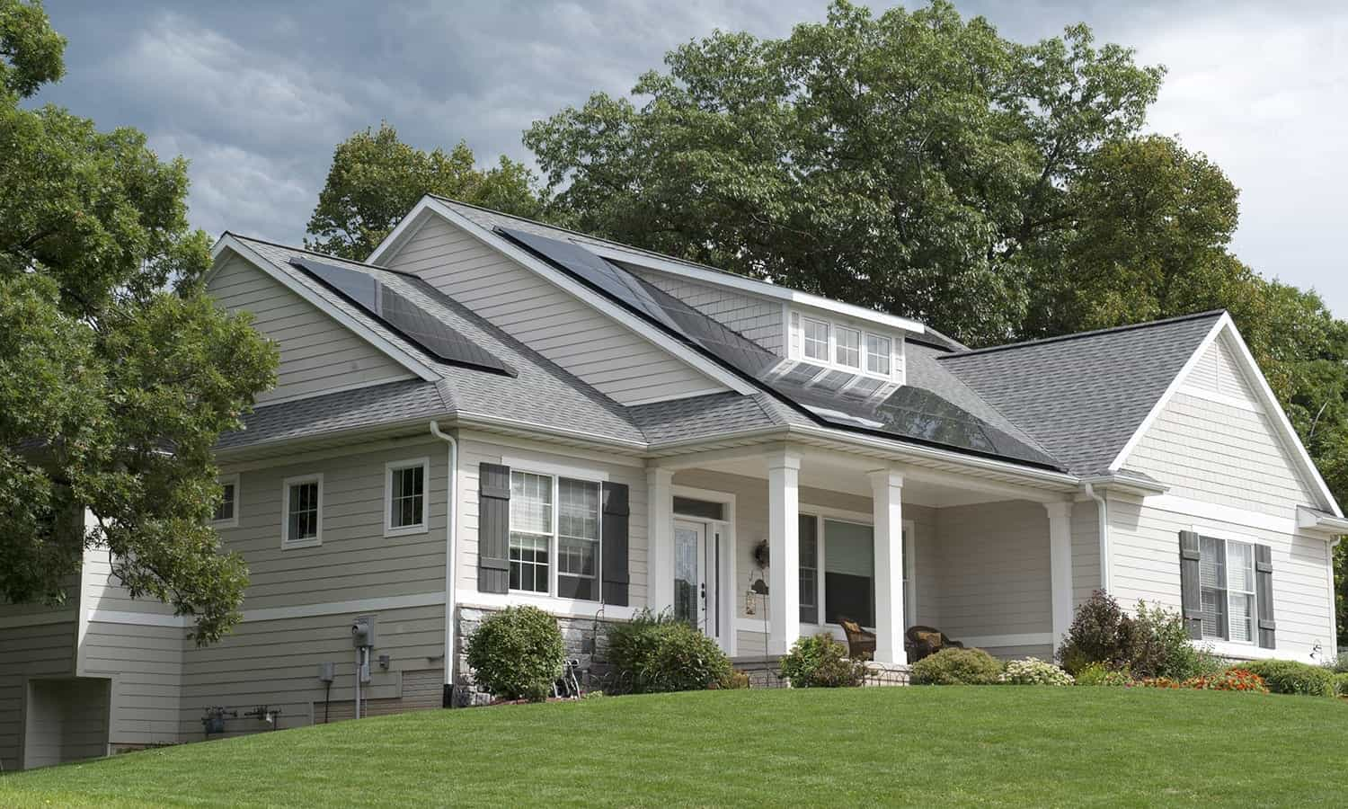 large modern home with frameless solar panels on roof