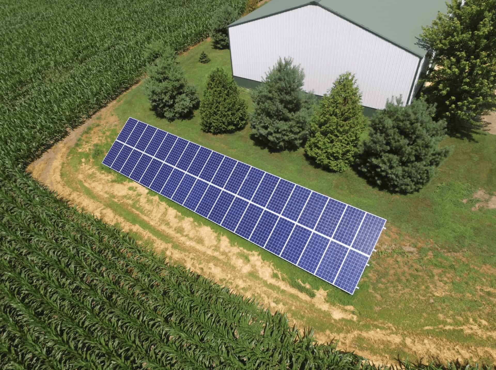 ground mount solar panel system next to corn field and pole building