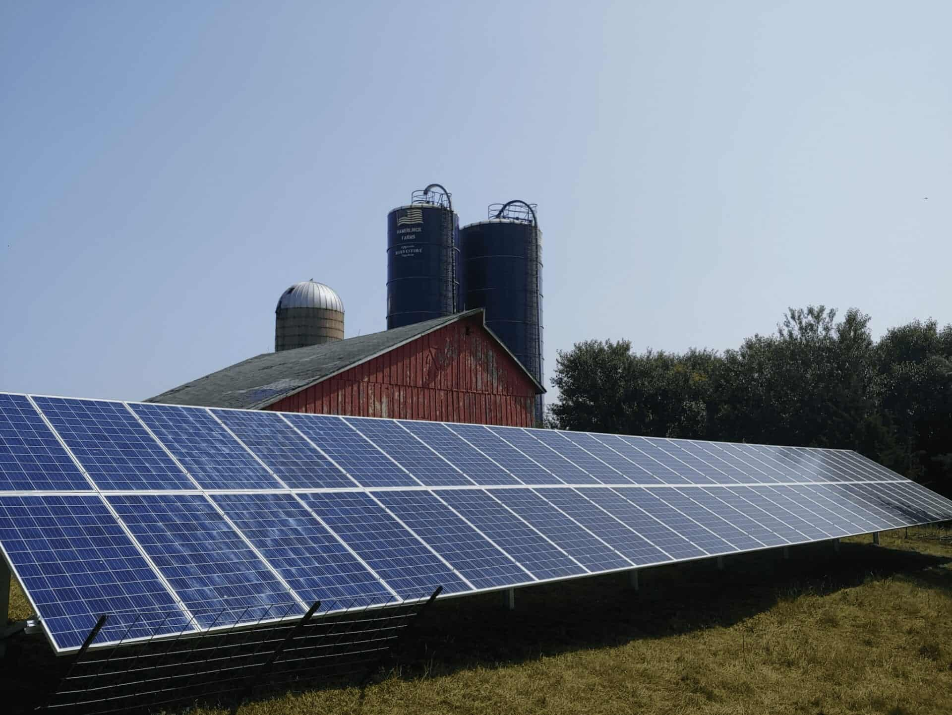 beautiful blue solar panel system next to barn and silos