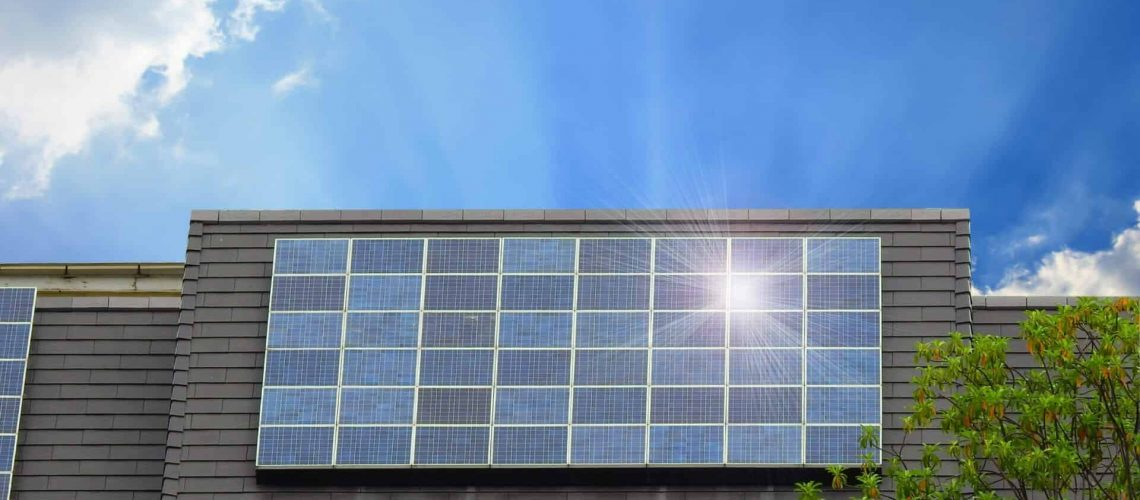 Green energy of solar cell panel on house roof in blue sky and sunlight